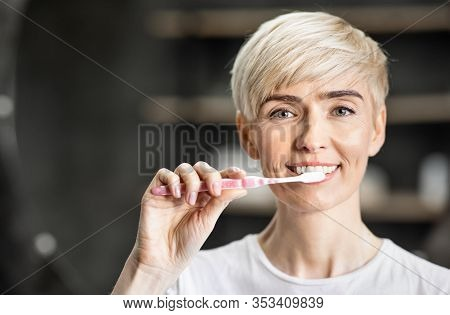 Oral Care. Woman Brushing White Teeth Smiling To Camera Doing Toothcare Routine Standing In Bathroom