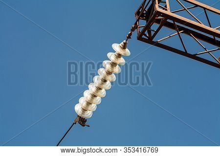 High-voltage Insulator On The High Voltage Line. Photographed On A Fon Of A Blue Sky