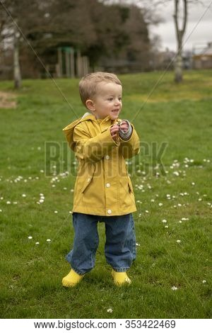 Vertical Image Of A Two Year Old Boy In Yellow Raincoat And Welly Boots Playing Outdoors