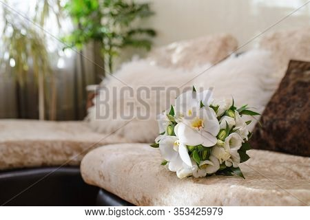 A Delicate And Beautiful Bridal Bouquet Of White Orchids And Red Roses Lying On The Sofa In The Room