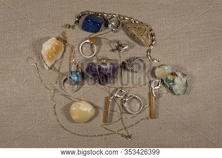 On A Beige Background Lie Silver Earrings And Rings And Chains Of Gold And Silver. Nearby Are The Se