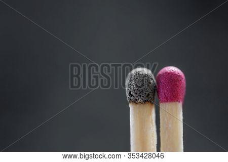 A Burnt Matchstick Close To A Fresh Unused Matchstick