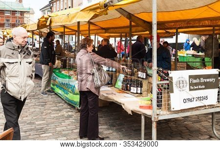 Uk-april 19, 2014: Female Shopper At Farmers Market Buying A Traditional English Bottled Ale From Fl