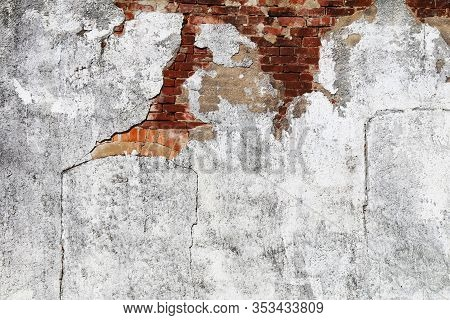 A Faded White Concrete Wall With Exposed Red Brick Details With Bright Sunlight Shadows