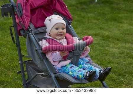 Smiling Baby In A Stroller On The Grass, Baby Girl Smiling In Spring In A Stroller