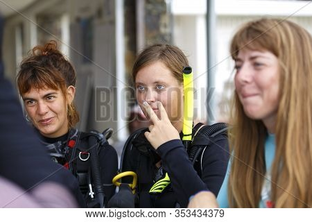 Group Of Scuba Divers On The Beach Listening To Instructions Before The Dive. Female Divers In Dive
