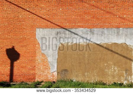 An Exterior Red And Orange Brick Wall With Grass Verge On A Bright Sunny Afternoon With Lamp Post Ca