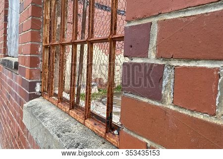 Looking Through Rusted Old Bars And Brick Wall Into An Abandoned Building Site