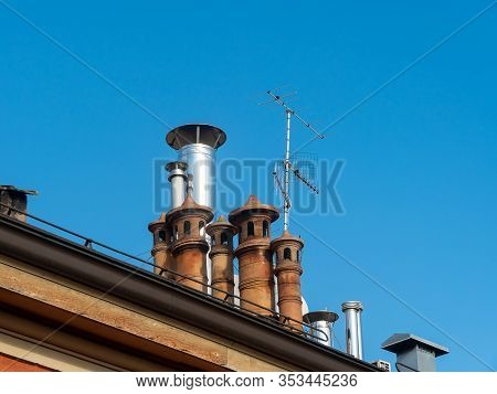 The Flues On The Roof Of An Apartment Building In Italy. Blue Sky Background