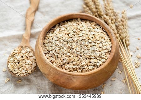 Oat Flakes, Rolled Oats In Wooden Bowl. Healthy Food Ingredients, Low Carb Dry Cereals For Porridge,