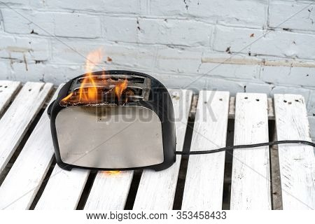 Burning Toaster. Toaster With Two Slices Of Toast Caught On Fire Over White Background. Danger Of Ca
