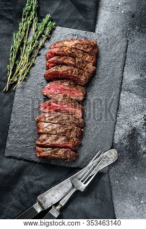 Grilled Roasting Rare Sliced Vegas Strip Steak. Marble Meat Beef. Black Background. Top View