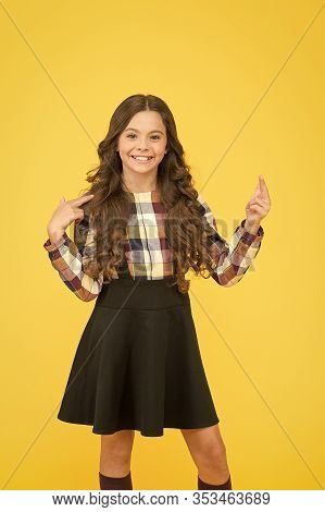 Look Up. Happy Girl In School Fashion Pointing Finger Up. Small Child Smiling And Pointing Yellow Ba