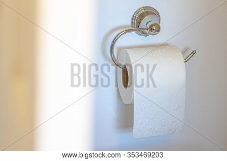 Single Post Toilet Paper Holder On A White Wall Background With Soft Shadow And Defucus Door