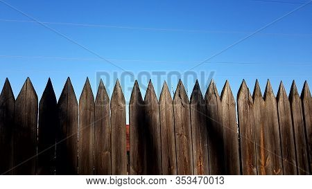 Fence Made Of Sharp Wooden Stakes. Blue Clear Sky In Sunny Day.