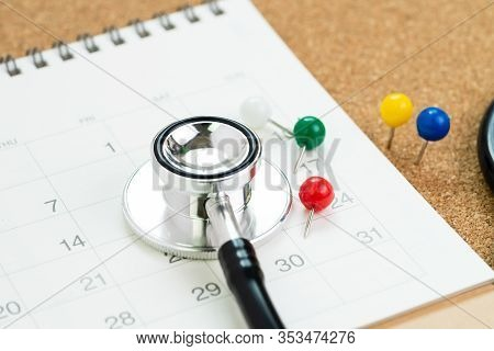 Stethoscope With Colorful Thumbtack Or Pushpin On White Calendar, Schedule Or Appointment For Medica
