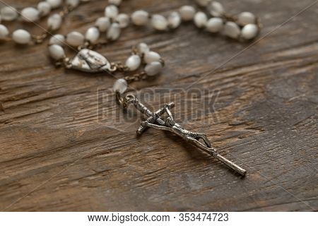 Catholic rosary at an old wooden table close up