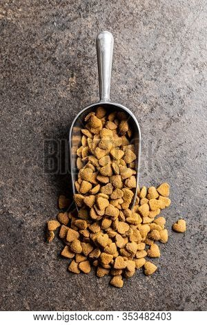 Dried kibble pet food in scoop. Heart shape dried animal food on old table. Top view.