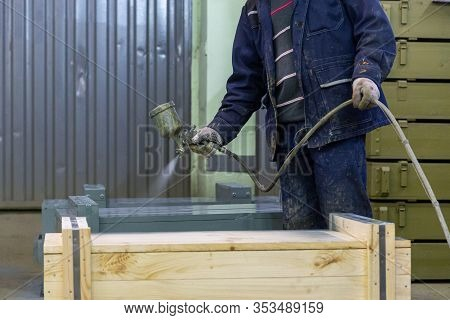 Worker With Airbrush Painting Big Wooden Crates To Gray Color