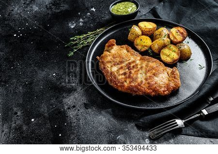 Breaded German Weiner Schnitzel With Potatoes. Black Background. Top View. Copy Space