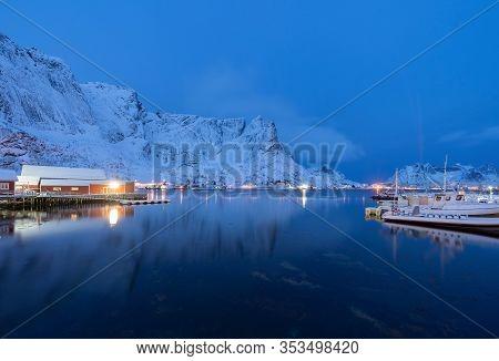 Norwegian Fishing Village In Reine City, Lofoten Islands, Nordland, Norway, Europe. White Snowy Moun