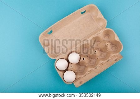Egg Chicken Eggs. Top View Of An Open Gray Box With White Eggs. Isolated On A Blue Background. The C