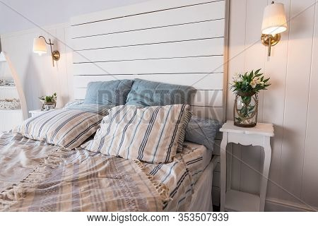 Contemporary Bed Dressed With Pastel Colored Cushions And Handing Lamp.vase With Spring Flowers Stan