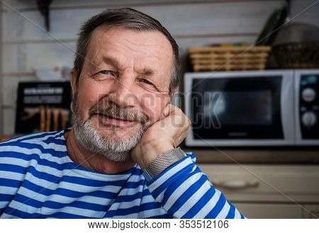 An elderly smiling Russian male pensioner in a vest in his room