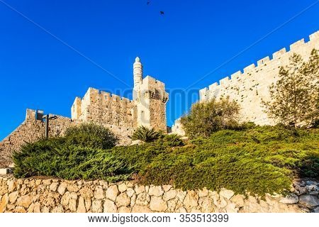 Monumental walls of Jerusalem. The height of the walls is 12 meters. Ancient Citadel - Tower of David. Hot summer sunset. The concept of historical, religious, pilgrim and photo tourism