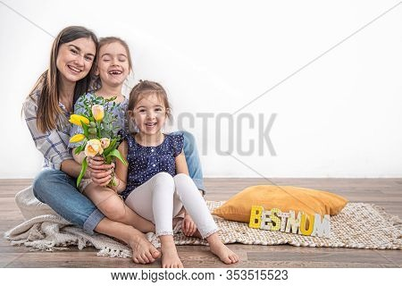 Two Little Sisters Congratulate Their Mom With Happy Mother's Day. Children Hugging And Kissing Moth