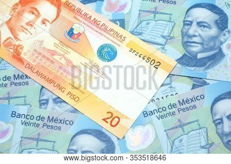 An Orange Twenty Piso Bank Note From The Philippines With Mexican Twenty Peso Bank Notes Close Up In