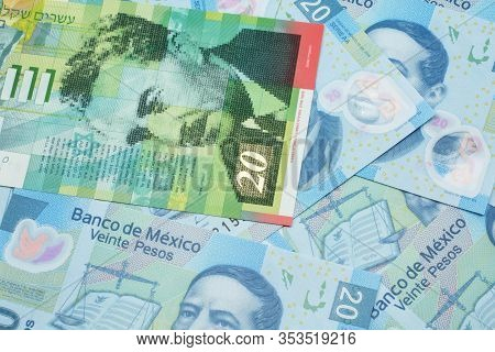 A Close Up Image Of A Twenty Shekel Bank Note From Israel On A Background Of Mexican Twenty Peso Ban