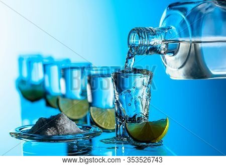 Tequila, Salt And Lime Slices On A Blue Background. Pouring A Strong Alcoholic Drink Into Small Glas