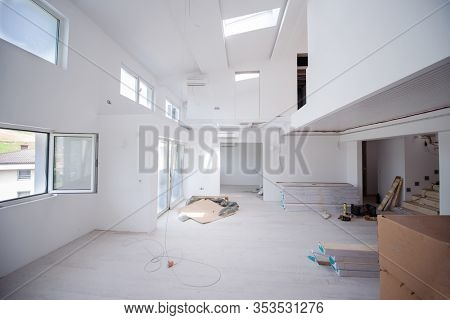 Interior of unfinished stylish modern open space two level apartment with white walls soon ready to move in