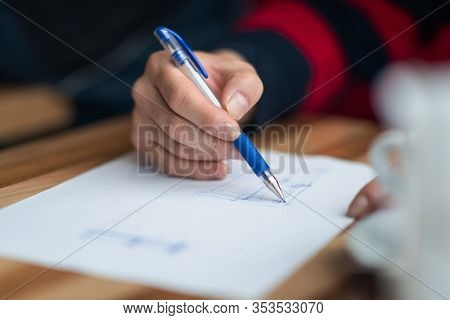 The hand of the designer with a pen, designing and sketching his idea for a furniture product