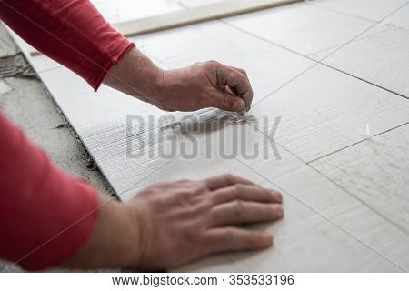 skilled worker installing the ceramic wood effect tiles on the floor Worker making laminate flooring on the construction site of the new apartment
