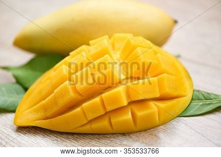 Mango Slice And Mango Leaves From Tree Tropical Summer Fruit Concept / Sweet Ripe Mangos Cut Half
