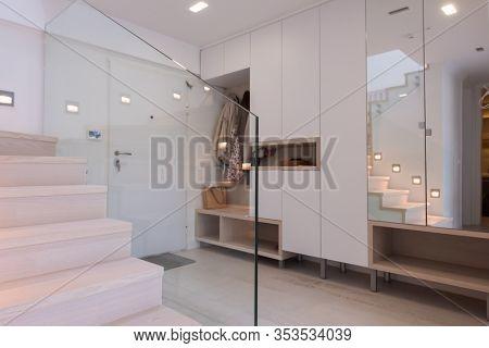 Stylish Interior of apartment entrance corridor with mirror and wardrobe