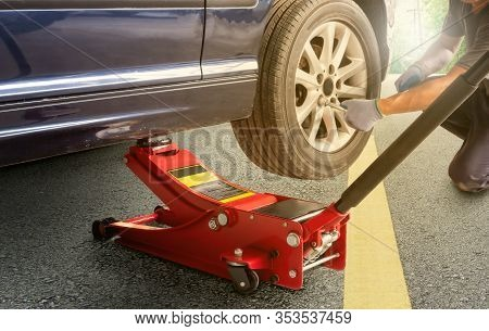 Red Hydraulic  Floor Jack ,asia Man With A Blue Car That Broke Down On The Road.changing Tire On Bro