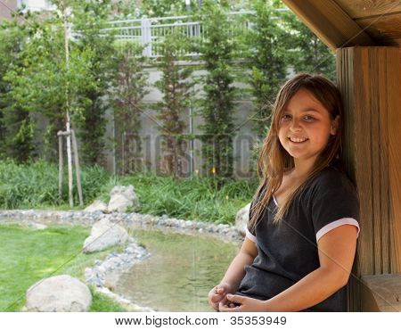 Young Girl Relaxing In Wooden Structure