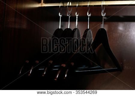 Wooden Clothes Hanger. Many Wooden Black Hangers On A Bar. Concept Store, Sale, Design, Empty Hanger