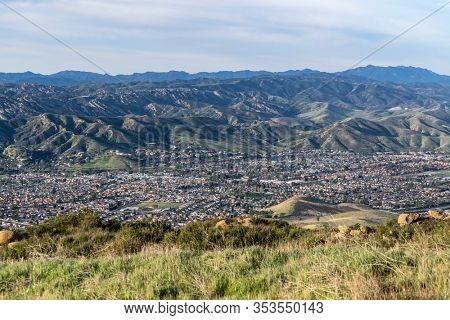 Grassy mountaintop cityscape view of streets and homes in suburban Simi Valley, California.