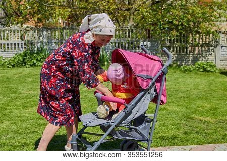 Grandmother Putting Baby In Stroller, Older Woman Puts Her Granddaughter In A Stroller, Grandmother