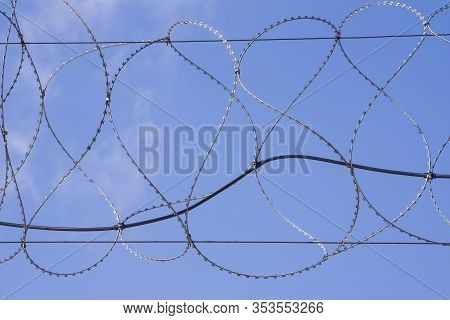Coiled Razor Wire With Its Sharp Steel Barbs On Top Of A Wire Mesh Perimeter Fence Ensuring Safety A