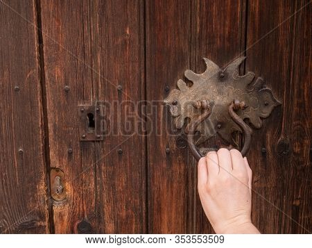 Female Hand With Black Iron Knocker On Retro Old Wooden Door. The Hand Knocks On The Door. Close Up,