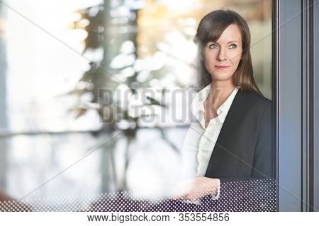 Businesswoman in corporate workplace taking break and drinking coffee while standing at office window. Looking away, thinking, daydreaming.