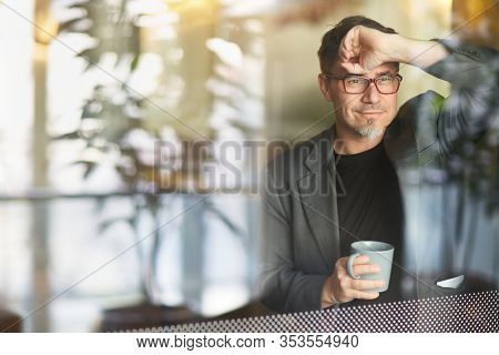 Older businessman in corporate workplace taking break and drinking coffee while standing at office window, daydreaming, thinking.