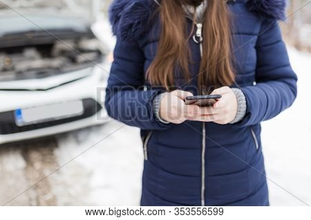 Female Using Smart Phone Against Car With Opened Hood On Winter Day. Roadside Assistance Service Con