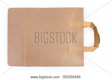 Folded Paper Shopping Bag With Paper Handles Made With Light Brown Unbleached Paper Close-up On A Wh