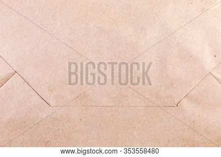Fragment Of Folded Glued Flat Bottom Of Brown Unbleached Paper Bag Close-up, Texture, Background